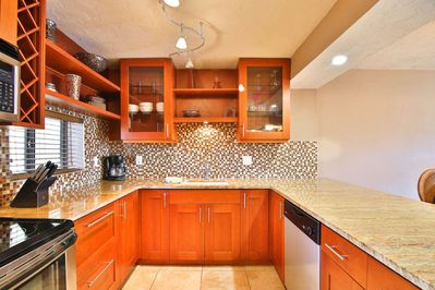 Beautiful new kitchen with glass front cabinet doors, stainless, and granite