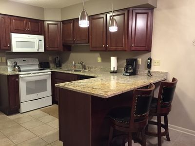 Newly remodeled kitchen with new appliances, granite top counter with bar stools