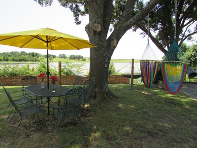 outdoor seating for 6 with 2 hammocks with 2 additional swings with lake view