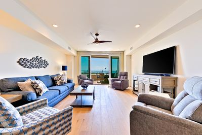 Ocean view beach chic living room with lots of comfortable seating, large flat screen TV, and easy access to the outside patio.