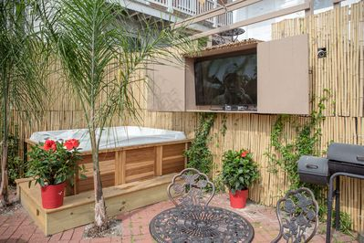 Communal outdoor courtyard w/ jacuzzi, BBQ pit, tables & chairs.