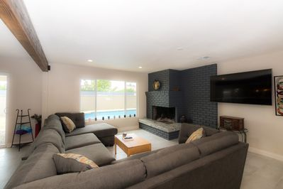 View of the living room, with pull out sleeper couch.  With a view of the pool.