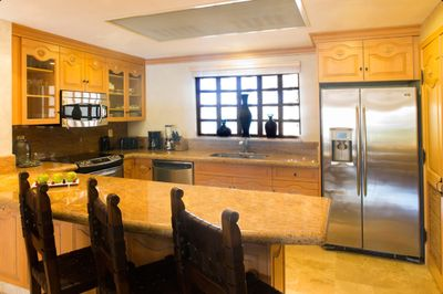 Full kitchen with modern appliances and marble counter tops.