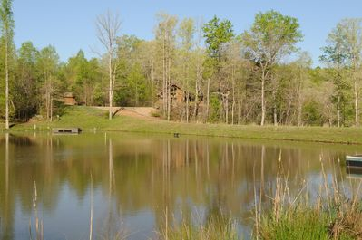 The cabin is tucked into the woods, facing the fishing pond, the river behind it