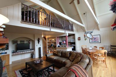"""Huge couch surrounding stone fireplace and 42"""" TV.  Table seats 6 - 8."""