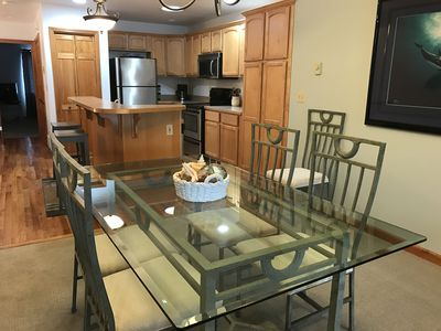 Beautiful glass top dining table seats 6 with additional seating at the island.