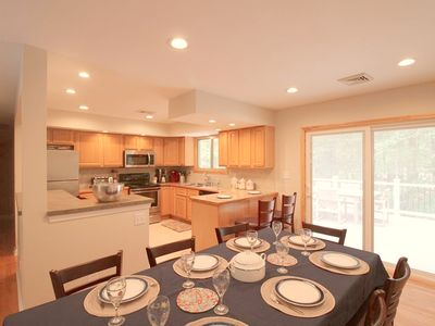 Dining/kitchen with sliding doors to deck with outdoor seating and grill