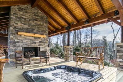 Covered deck with fireplace and hot tub