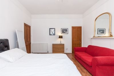 Master bedroom with King size bed.  a sofa bed and Tv