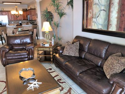 Living Room-Comfy leather furniture with direct access to the 300 sq ft balcony.