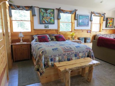 Beautiful Moose and Bear Quilt surrounded by original paintings and furniture.