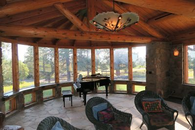 Large Piano Room featuring stone floor and walls, baby grand, and chandelier.