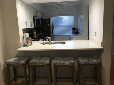 Kitchen with stools to sit and enjoy a quick meal.