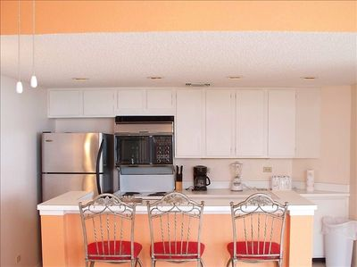 Full kitchen with additional bar stools, appliances and stainless steel fridge