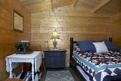 The Interior of the Bunkie features a writer's desk, Lamp, Dresser and Bed