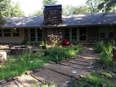 Cabin Exterior. Front herb beds and stone fire pit.