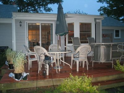 Outside deck includes patio furniture and grass grill