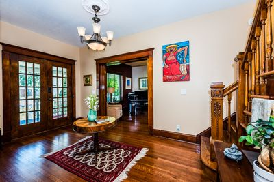 Inviting foyer with original woodwork and French pocket doors.