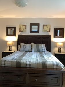 Bedroom with comfy queen bed, double closets, black-out curtains, luggage racks