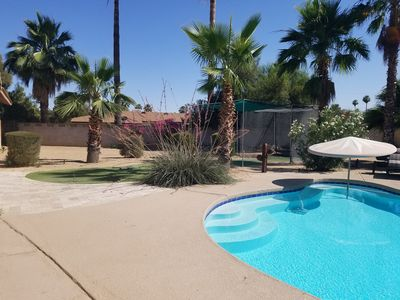 Spacious backyard, features sparkling pool, outdoor dining,  and a putting area