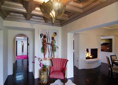 Lobby with carved ceiling, open fireplace between kitchen and dining room, right