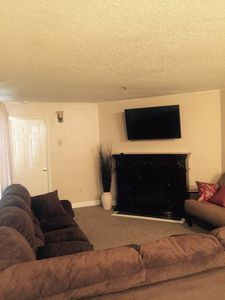 Comfy large sectional, Smart TV, futon next to heat emitting electric fireplace.