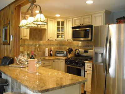 Stainless steel and granite adorn this thoroughly updated and modern kitchen