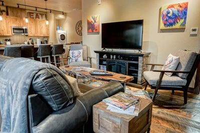 Large flat screen TV in an open living room with cozy seating for all.