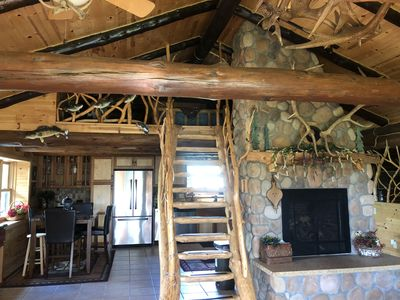 View of fireplace, loft and kitchen in the back. Antler mount and chandelier.