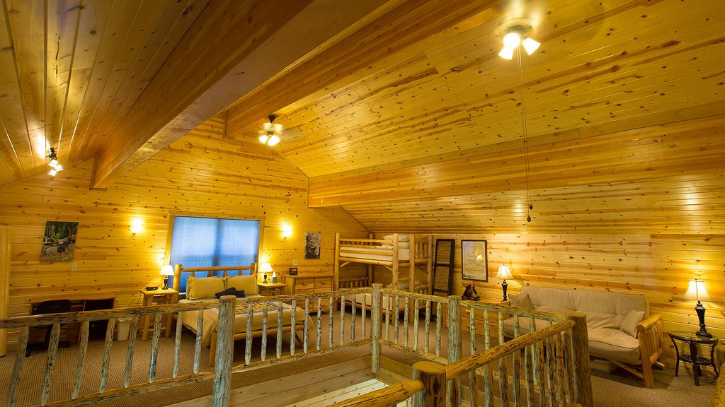 The loft, with a queen size bed, twin bunk beds, futon, desk and library.