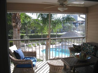 View of Pool Area from Screened Lanai which has Comfortable and Spacious Seating