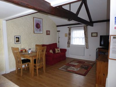 """The cosy open plan living and dining area with 43"""" smart TV and exposed beams"""