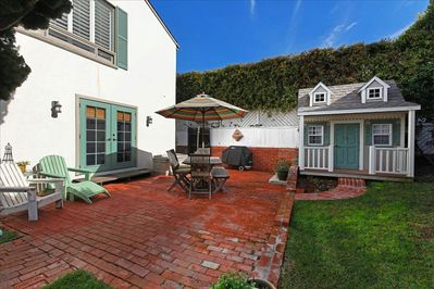 Gated side patio with  weber BBQ ,play house with  working lights .