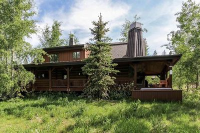Side exterior of chalet surrounded by trees and lawn