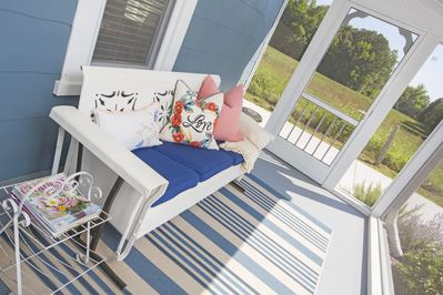 Enjoy the charming screened front porch with antique glider and comfy pillows.