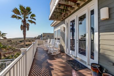 Second floor deck has four  Pollywood rocking chairs and bar height patio set