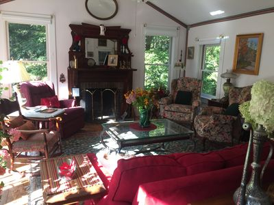 Large living room with fireplace, 6 french doors, 6 windows, overlooks backyard