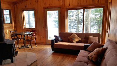 Living room area with two futons, wood burning stove and radiant heating