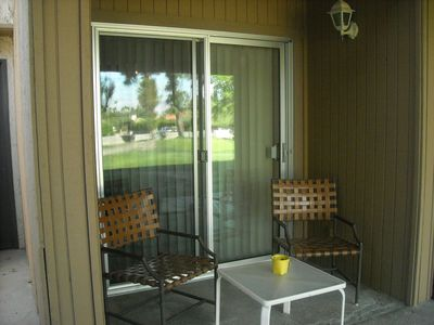 Outside patio space with 2 chairs and small table. You can smoke in outside.