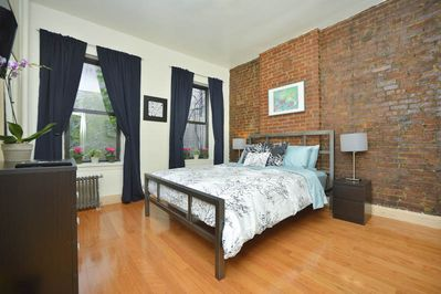 Bedroom with queen-size bed and original exposed brick wall.