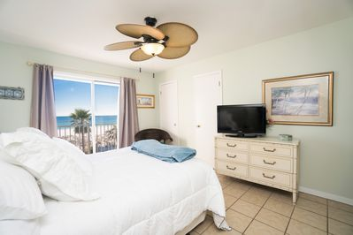 Spacious master bedroom with balcony looking out towards beach.