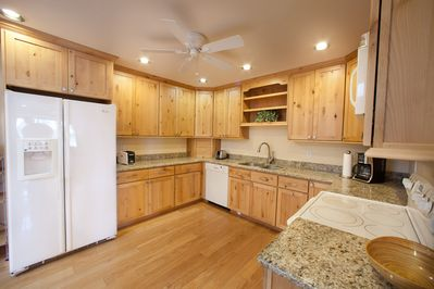 Spacious kitchen with hardwood floors and granite counter tops.