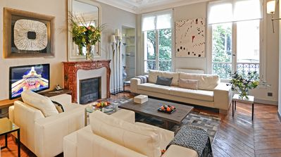 Living room with solid oak wood floor, marble fireplace and original moldings.