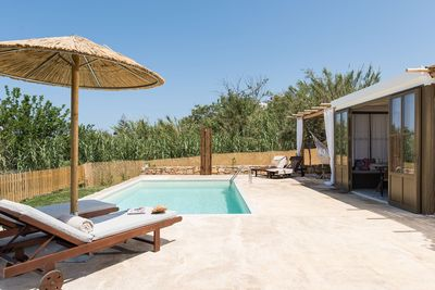 The pool terrace is equipped with sun beds, umbrellas and an outdoor shower.