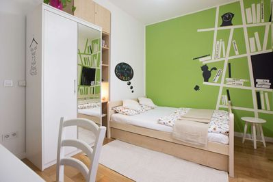 Living space with double bed and art painting over the whole wall.