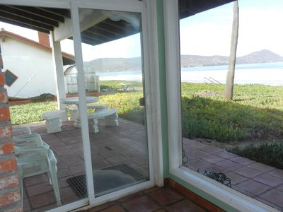 beachside sliding door to the patio with table and seating for watching the view