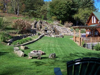 View of 34 ft waterfall and fire pit, back deck, gas grill and outdoor furniture