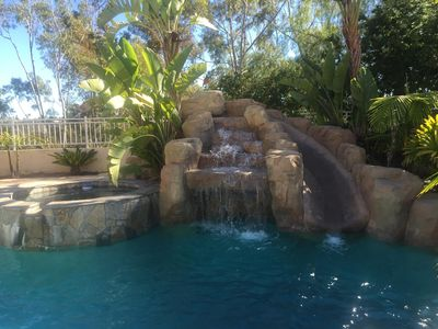 Swimming pool with slide, hot tub and waterfall features.
