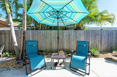 Relax on one of the chaise lounges under a sunbrella.