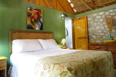 The room features a natural rock wall and locally made bamboo furnishing.